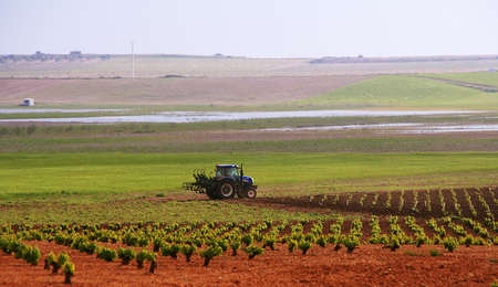 Farming tractor plowing and spraying fields photo