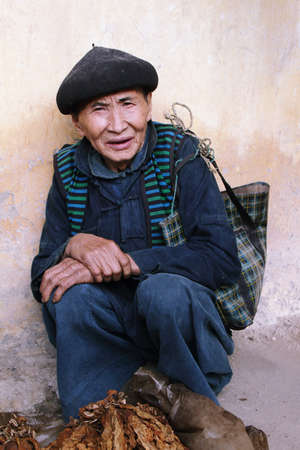 HA GIANG, VIETNAM  - DECEMBER 7  Unidentified old man selling tobacco leaves in Lung Phin market  Lung Phin market is one of the most typical hill tribe markets in Vietnam