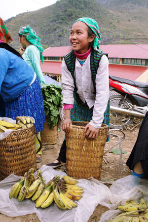 national fruit of china: HA GIANG, VIETNAM  - DECEMBER 7  Unidentified young girl selling bananas in Lung Phin market  Lung Phin market is one of the most typical hill tribe markets in Vietnam