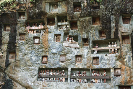 cliff face: Indonesia, Tana Toraja - Londa, is a very extensive burial cave at the base of a massive cliff face The entrance to the cave is guarded by a balcony of tau tau