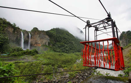 Red Tarabita and Manto de la novia (bridal veil) waterfall at background in Cascades route near Banos, Ecuador photo