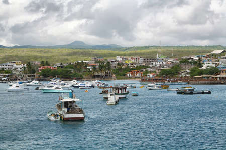 inhabited: GALAPAGOS, ECUADOR - APRIL 29: Views of boats and houses arriving at colorful Puerto Baquerizo Moreno in San Cristobal island. Puerto Baquerizo is one of only 2 inhabited port cities in Galapagos island.
