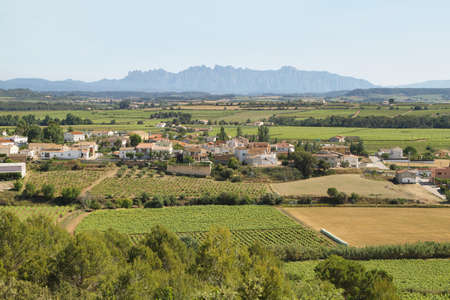 Panoramic landscape with a small village surrounded by vineyards and Montserrat multi-peaked mountain at background, Barcelona, Catalonia, Spain.