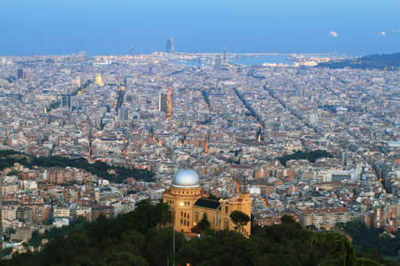 Barcelona skyline at dusk with Fabra observatory at foreground and harbor at background photo