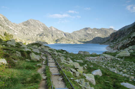 Lake Llong and old railroad track for miners in Aiguestortes national park, Spain photo