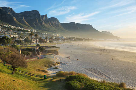 and south: Camps Bay Beach in Cape Town, South Africa, with the Twelve Apostles in the background. Stock Photo