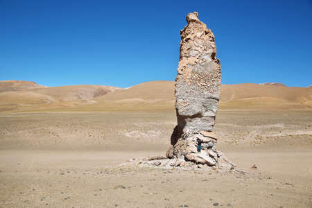 witnesses: Geological monolith Known as Monjes de la Pakana close to Salar Aguas Calientes with a person in its base, Atacama desert, Chile