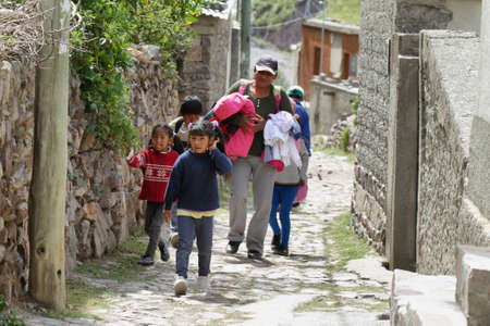 isidro: SAN ISIDRO, ARGENTINA - APRIL 7: Indigenous woman and kids in the narrow streets of the remote village of San Isidro on April 7, 2015 in San Isidro, Salta province, Argentina. No roads arrive to this remote village.