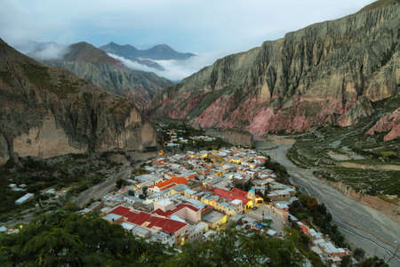 View of Iruya village and multicolored mountains in the surroundings at sunset, Salta province, Argentina