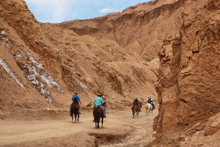 marte: SAN PEDRO DE ATACAMA, CHILE - APRIL 12: People riding horses on April 12, 2015 in Valley of Mars near San Pedro de Atacama, Chile