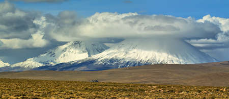 cloud capped: View of snow-capped Parinacota and Pomerape volcanoes known as Payachatas, Chile