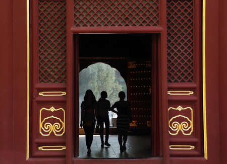 eligion: Silhouettes of girls inside Lama Temple Yonghe Lamasery in Beijing, China.