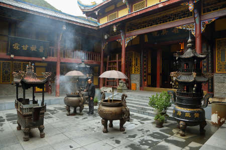 caretaker: HUANLONG, CHINA - SEPTEMBER 11, 2015: Caretaker  of Huanglong Ancient Temple in interior courtyard, Huanlong scenic Area, Unesco world heritage site in Sichuan Province, China