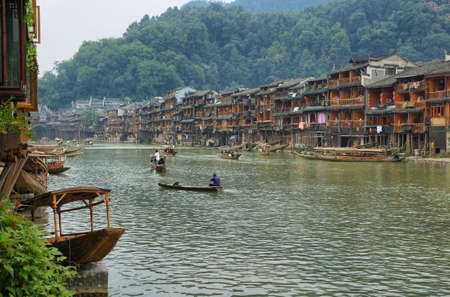 chinese phoenix: FENGHUANG, CHINA - SEPTEMBER 16, 2015: View of riverside houses, boats with tourist people in ancient town of Fenghuang known as Phoenix, China