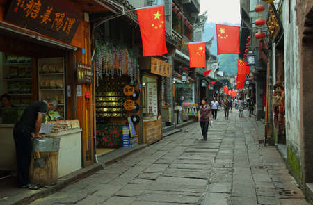chinese phoenix: FENGHUANG, CHINA - SEPTEMBER 16, 2015: People walking in a commercial street in ancient town of Fenghuang known as Phoenix, China