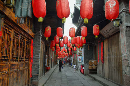 garish: FENGHUANG, CHINA - SEPTEMBER 16, 2015: People walking in a nice decorated street in ancient town of Fenghuang known as Phoenix, China
