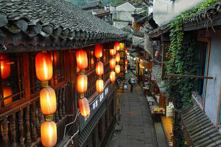 ave fenix: FENGHUANG, CHINA - 15 de septiembre, 2015: La gente que camina en una calle iluminada con hermosas lámparas de color rojo en la antigua ciudad de Fenghuang conocido como Phoenix, China