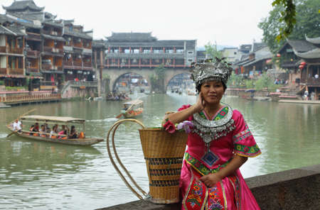 house float on water: FENGHUANG, CHINA - SEPTEMBER 16, 2015: Woman disguised posing with riverside houses and boats at background in ancient town of Fenghuang known as Phoenix, China Editorial