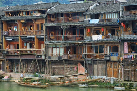 chinese phoenix: FENGHUANG, CHINA - SEPTEMBER 16, 2015: View of riverside houses beside Tuo river in ancient town of Fenghuang known as Phoenix, China