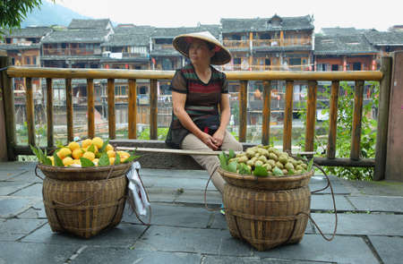 chinese phoenix: FENGHUANG, CHINA - SEPTEMBER 16, 2015: Woman selling fruits with riverside houses at background in ancient town of Fenghuang known as Phoenix, China Editorial