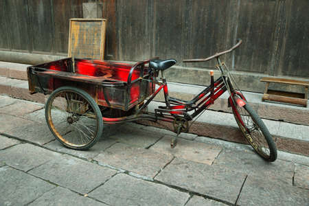 chinese phoenix: Red tricycle parked in a deserted street of Fenghuang ancient village, China