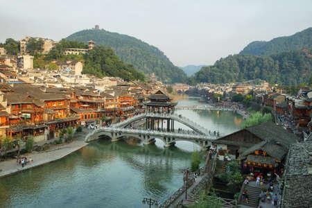 ave fenix: FENGHUANG, CHINA - 16 de septiembre, 2015: Vista del puente de piedra sobre el río Tuo Jiang y casas de madera en la antigua ciudad de Fenghuang conocido como Phoenix, China