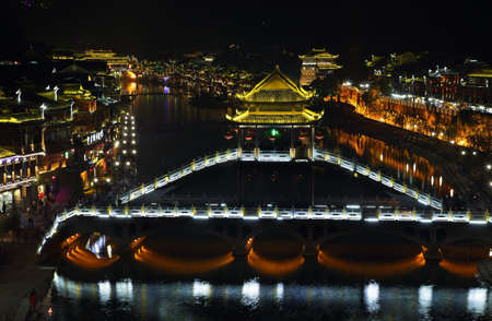chinese phoenix: FENGHUANG, CHINA - SEPTEMBER 15, 2015: View of illuminated stone bridge over Tuo Jiang river and wooden houses in ancient town of Fenghuang known as Phoenix, China