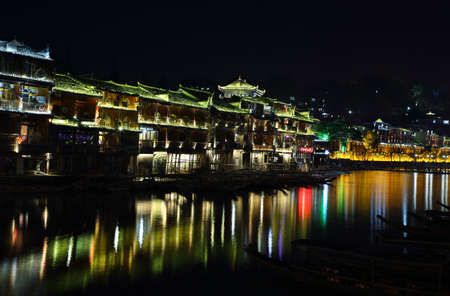 house float on water: FENGHUANG, CHINA - SEPTEMBER 15, 2015: View of illuminated riverside stilt houses in ancient town of Fenghuang known as Phoenix, China