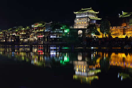 house float on water: FENGHUANG, CHINA - SEPTEMBER 16, 2015: View of illuminated riverside houses in ancient town of Fenghuang known as Phoenix, China Editorial