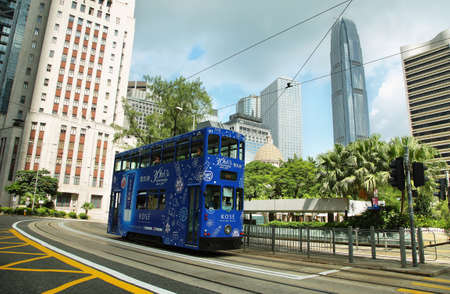 ifc: HONG KONG, CHINA - SEPTEMBER 23, 2015: Bus traveling in a central street with ifc tallest building at background in Hong kong island.