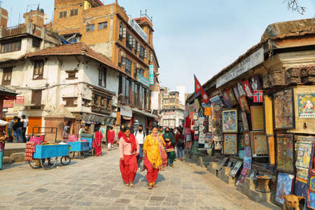 flashy: KATHMANDU, NEPAL - APRIL 9 2016: hinduism people dressed with flashy clothes walking in a commercial sector near Durbar Square of Kathmandu in Nepal.