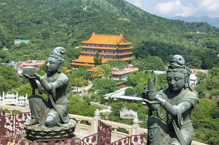 Buddhist statues praising and making offerings to the Tian Tan Buddha with Po Lin Monastery at background in Lantau island, Hong Kong.