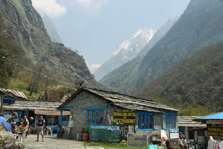 midday: HIMALAYA, NEPAL - APRIL 15, 2016: trekkers resting at midday with Annapurna range peaks at background in Himalaya village, Nepal