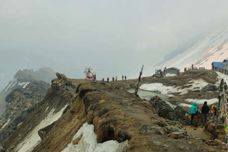 lodges: ANNAPURNA SANCTUARY, NEPAL-APRIL 16, 2016 Hikers are watching a helicopter that is landing in abc to bring supplies to the lodges in Annapurna base camp Sanctuary, Nepal. Editorial