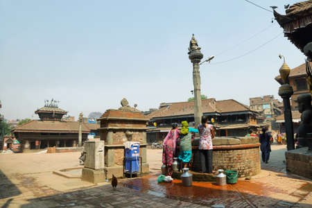 step well: BHAKTAPUR, NEPAL - APRIL 20, 2016: women collecting water in a water well in front of Dattatraya Temple in Tachupal Tole square, Bhaktapur, Nepal. Editorial