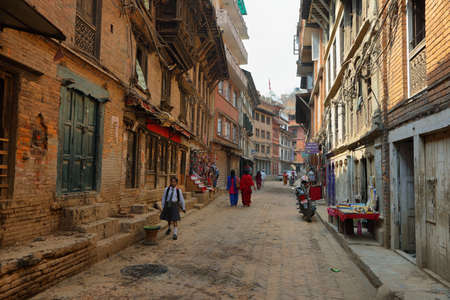 BHAKTAPUR, NEPAL - APRIL 20, 2016: hindu people dressed walking in a beautiful street of medieval town of Bhaktapur in Nepal.