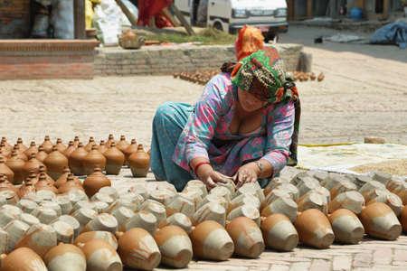 ollas de barro: Bhaktapur, Nepal - 20 de abril, 2016: Mujer hindú que trabaja en el stand de la cerámica en el medio de la plaza de la cerámica en la ciudad medieval de Bhaktapur, Nepal.