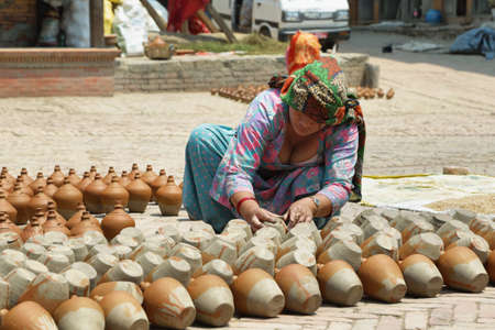 BHAKTAPUR, NEPAL - APRIL 20, 2016: hindu woman working in pottery stand in the middle of Pottery Square in medieval town of Bhaktapur, Nepal. Editorial