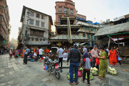 os: KATHMANDU, NEPAL - APRIL 20, 2016: women vendors selling vegetables in front os a hindu temple in the heart of the old town in Kathmandu, Nepal