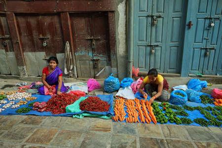 mujeres sentadas: KATMANDU, NEPAL - 20 de abril, 2016: las mujeres vendedores de verduras sentados en una calle en el coraz�n de la ciudad vieja en Katmand�, Nepal Editorial