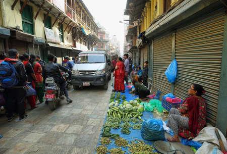 mujeres sentadas: KATMANDU, NEPAL - 20 de abril, 2016: las mujeres vendedores de verduras sentados en una calle muy transitada en el corazón de la ciudad vieja en Katmandú, Nepal