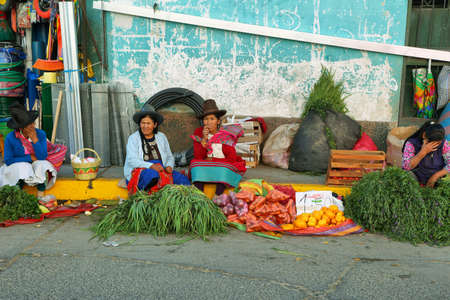 ancash: HUARAZ, PERU - JUNE 5: women selling herbs and fruits in small stall in a commercial street of Huaraz city on June 5, 2017 in Huaraz, Ancash province, Peru