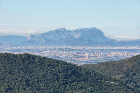 Landscape with Montserrat multi-peaked mountain at background and towns in the surrounding area, Barcelona, Catalonia, Spain.