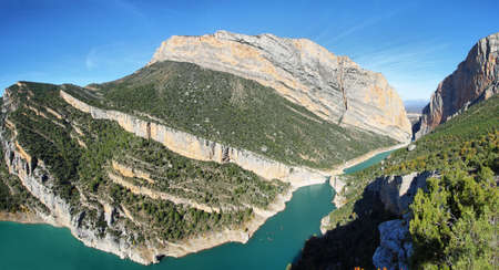 Spectacular cliff with a wooden walkway to be able to go down to a turquoise river. Montrebei Catalonia Stock Photo