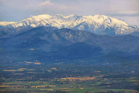 Snowed peak of Canigou mountains and meadow at foreground. Springtime. Eastern Pyrenees, France.