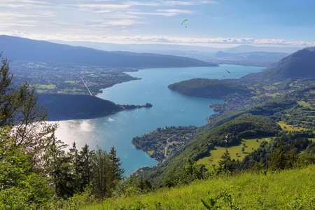 View of the Annecy lake and people doing paragliding from Col du Forclaz