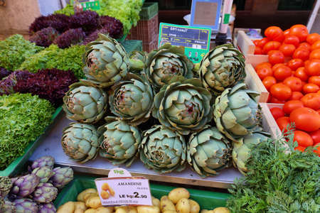 Artichokes and other vegetables in the market. Growing organic vegetables.