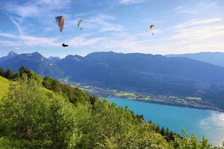 View of the Annecy lake and people doing paragliding from Col du Forclaz Reklamní fotografie