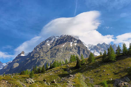 Spectacular Lenticular cloud over a mountain in Val Vény, Aosta Valley, Italy. Stock Photo