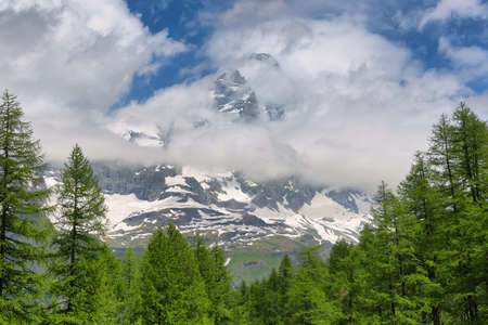 Summer alpine landscape with Matterhorn peak between the clouds near Breuil-Cervinia, Aosta Valley, northern Italy